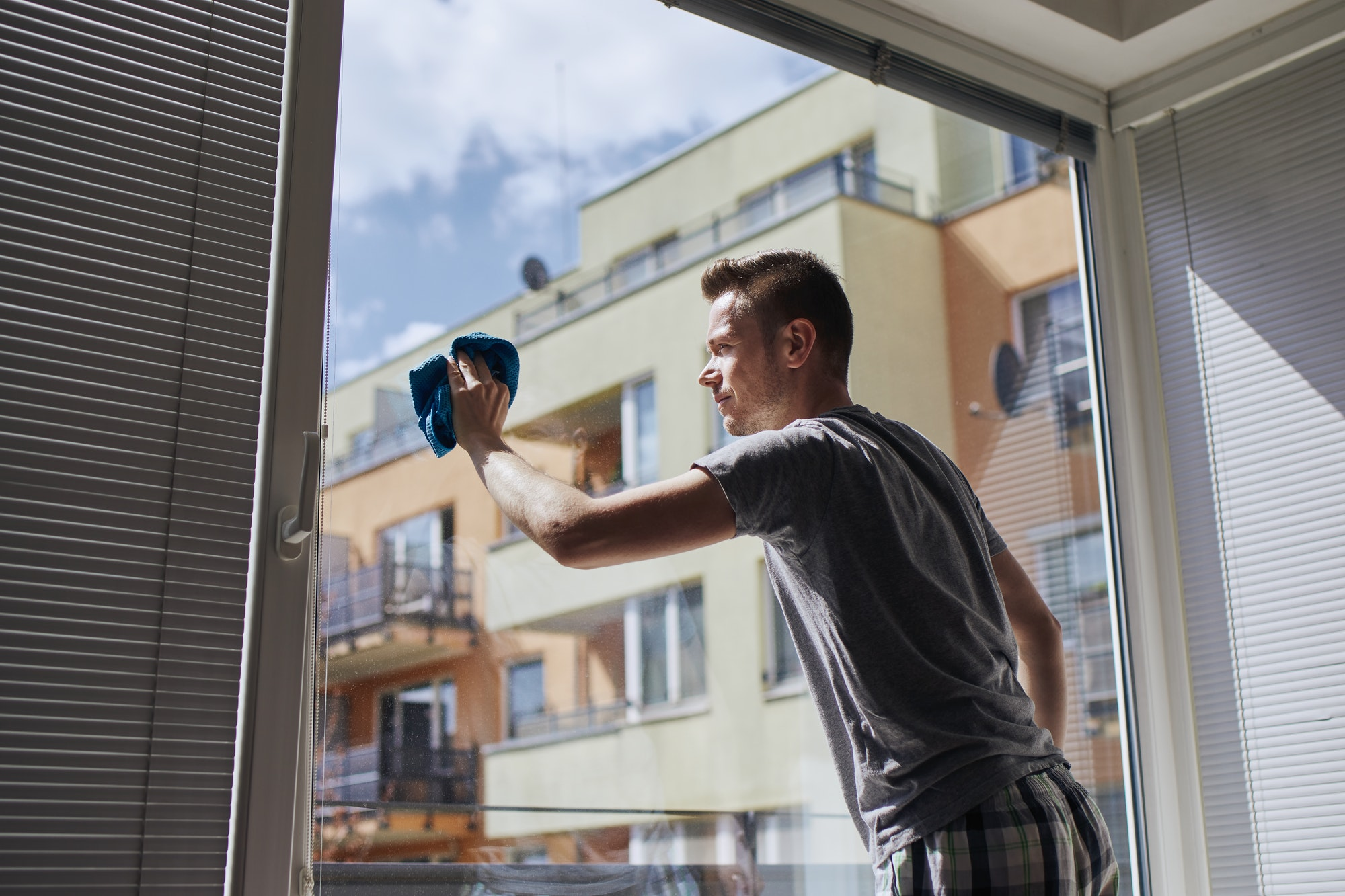 Man cleaning window at home